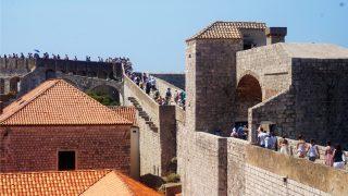 Een bezoek aan Dubrovnik is pas compleet wanneer je een wandeling over de spectaculaire stadsmuren hebt gemaakt. Ze vertellen het geschiedenisverhaal van Dubrovnik en geven je een unieke kijk in het verleden van de stad. De stadsmuren staan al sinds 1979 op de UNESCO Werelderfgoedlijst. Kom meer te weten over de historie van Dubrovnik en haar stadsmuren. Een stukje geschiedenis voor je vertrekt De muren en forten van Dubrovnik hebben door de eeuwen heen een belangrijke verdedigende rol gespeeld voor Dubrovnik. Ook tijdens de meest recente oorlog (1991/1992) liepen de oude stad en de stadsmuren veel schade op. Dubrovnik is in de 7e eeuw gesticht do or de inwoners van het stadje Epidaurum (nu Cavtat), zij waren op de vlucht voor binnenvallende slaven. Ze noemden de stad Ragusa. De Slavische naam voor de stad werd Dubrovnik. Na een tijd onder het Byzantijnse Rijk te hebben geleefd kwam Ragusa onder Venetiaans bestuur. Uiteindelijk werd Ragusa, bij de Vrede van Zadar (1359), onderdeel van Hongarije. Ragusa werd wel volledig zelf besturend en werd dus een vrije stadstaat. Gevolg: De stad werd ommuurd en voorzien van twee havens in Ragusa en Cavtat. De republiek breidde haar grondgebied steeds meer uit. Een einde aan de bloeiperiode van Ragusa Het hoogtepunt van de macht werd bereikt in de 15e en 16e eeuw. De zeemacht was op dat moment net zo machtig als die van Venetië en andere Italiaanse zeestaten. Echter kwam hier ook het keerpunt. Ragusa ondersteunde het Ottomaanse Rijk tegen de Portugezen tijdens de Slag van Diu. Deze slag werd verloren door het Ottomaanse Rijk, waardoor de handelsroute zich verplaatste van de Middellandse Zee naar Indië (dat was in handen van Portugal). De handelscrisis en een rampzalige aardbeving in 1667 maakten een einde aan de bloeiperiode van Ragusa. In 1699 bij de Vrede van Karlowitz werden er twee kleine grensgebieden van Ragusa geschonken aan het Ottomaanse Rijk. Dit om op die manier te voorkomen dat Venetië (in die tijd de grootste bedreig